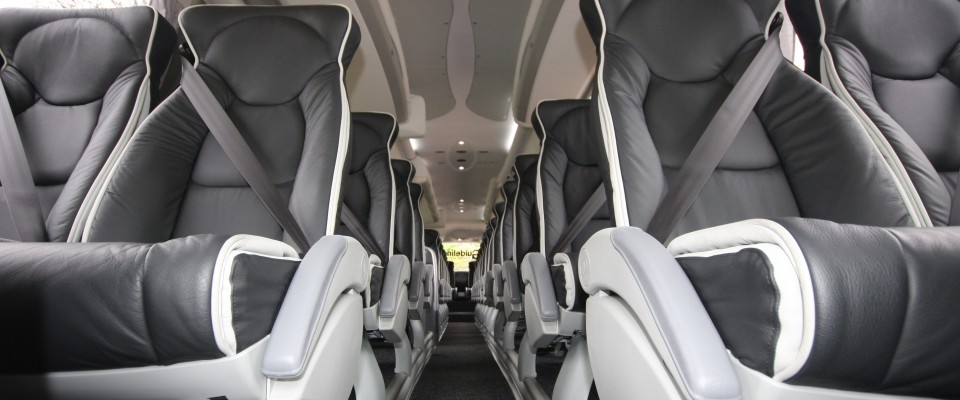 An image showing the front leather seats inside a Midi Coach available for hire by Guideline Coaches