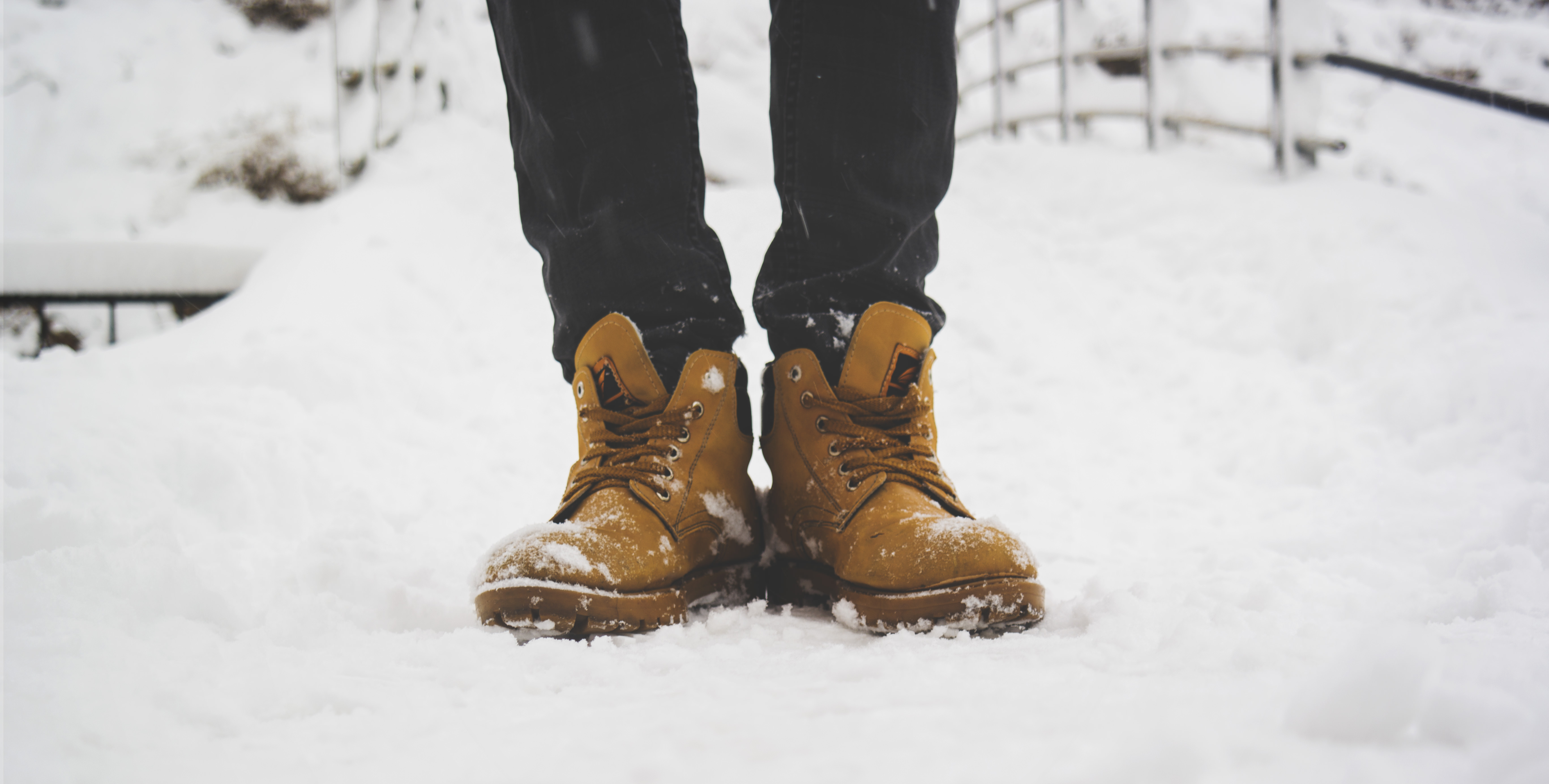 An image showing boots of a man who is stood in snow