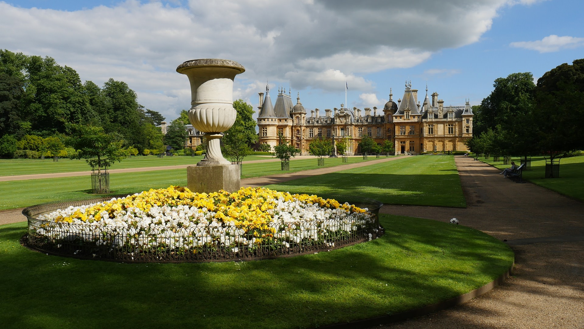 An image of a English country garden with a water fountain in the foreground and a castle in the background.