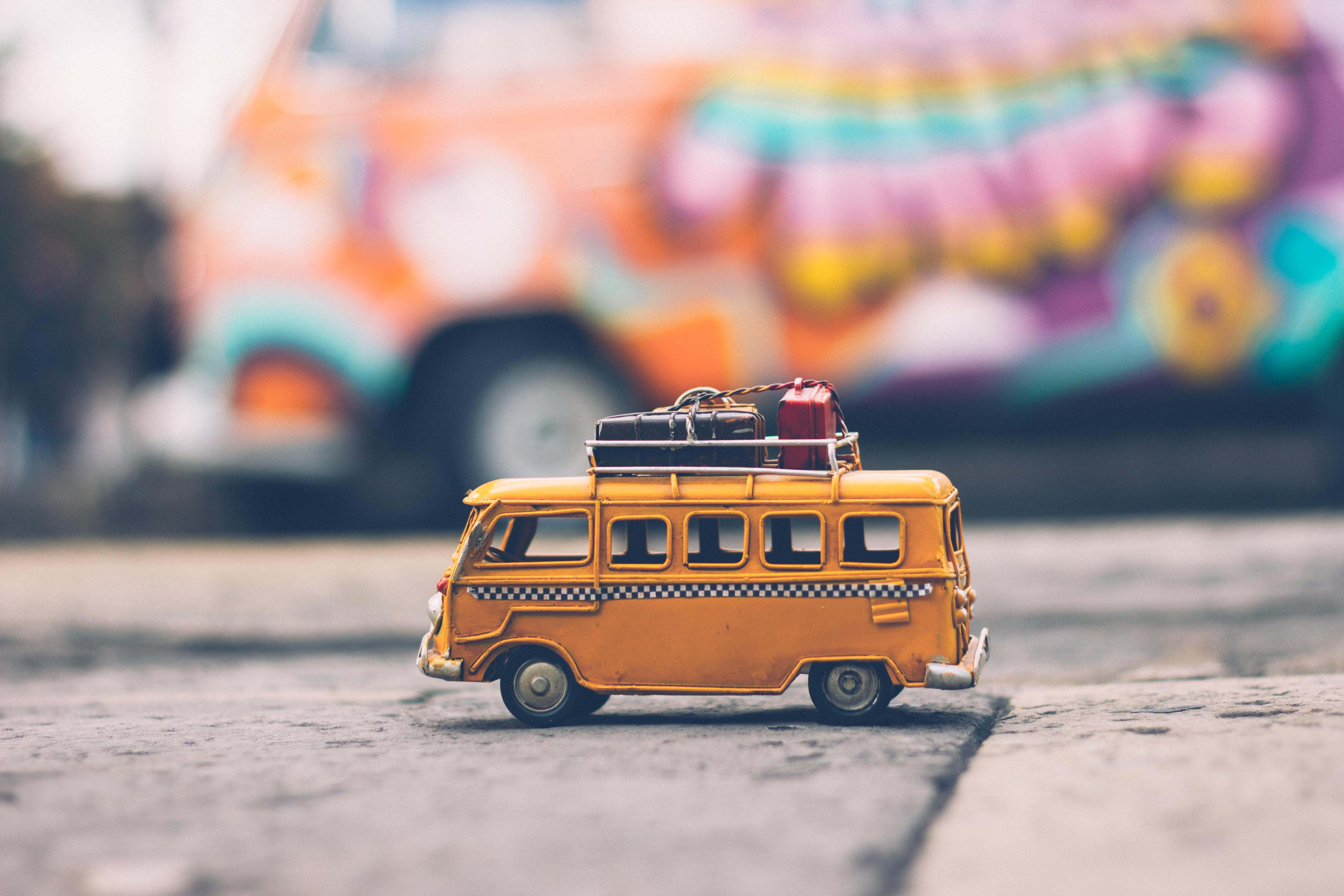 An image of a toy coach with pieces of toy luggage on strapped to the roof.